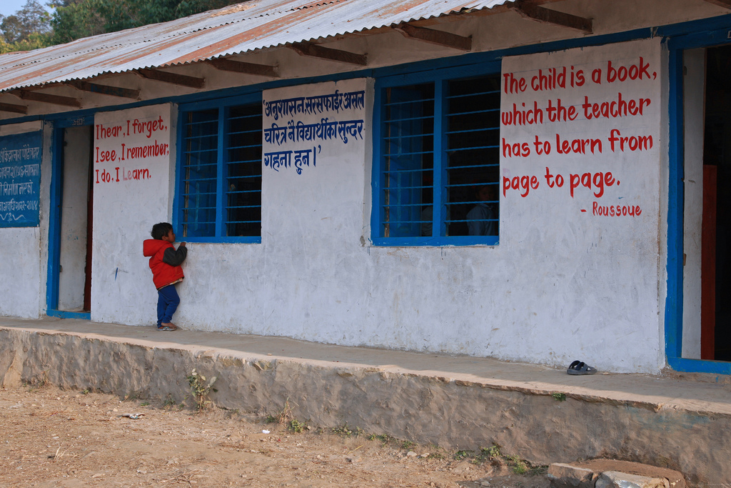 A child peeks through the window of a classroom
